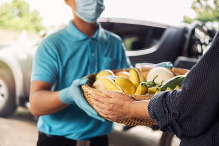 Senior woman hand receiving fresh fruits and vegetables in bamboo basket from delivery man wearing protective gloves and face mask. Food delivery in COVID-19 pandemic and senior people social care. 写真素材