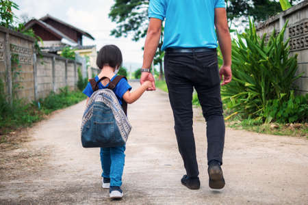 Little child with heavy backpack wearing cloth face mask holding father's hand walking to school, return to school in Coronavirus (COVID-19) pandemic. Imagens