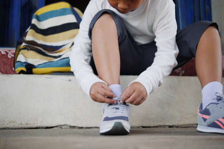 Asian schoolboy in casual clothing tying shoelaces on sneakers getting ready for school or traveling. 写真素材