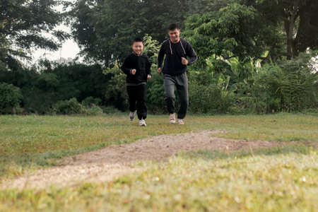 Asian preteen boy and young father jogging together in nature trail green forest park with slightly morning mist. Healthy lifestyles concept. 版權商用圖片