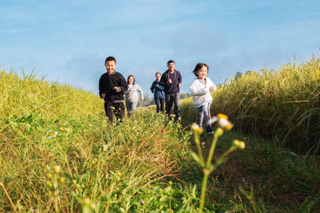 Small group of people multigeneration Asian family jogging together, outdoor morning run in nature trail organic rice paddy field. Healthy lifestyles and sustainability concepts. Stock Photo