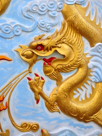 Ancient golden Chinese Dragon statue against blue sky photo