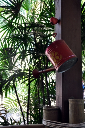 neighbourly: The old watering cans hanging on a wooden pole