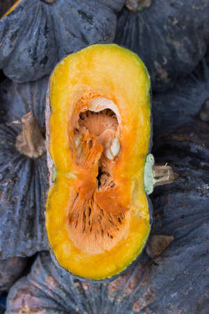 Fresh japanese pumpkin or kabocha with one piece cut out on farmers market photo
