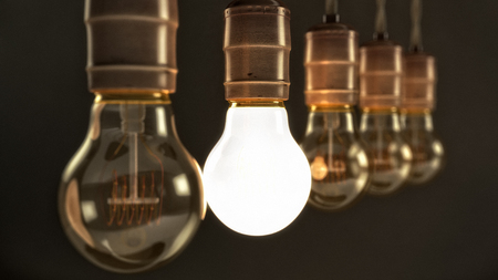 quintet: Five hanging vintage incandescent light bulbs over dark background with one illuminated