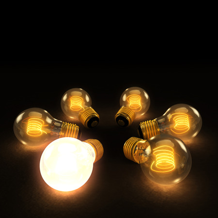 Six illuminated incandescent light bulbs in a circle on a dark background with one brighter