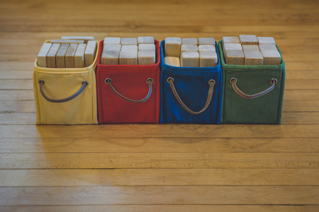 Four cloth bins  in primary colors with leather handles full of wooden toy blocks set in a straight line on a hardwood floor.