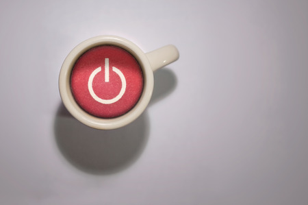 power button: A coffee mug with a red power button replacing the coffee.  A morning power up.  Installing java. Stock Photo