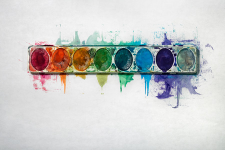 A watercolor paint tray on a white background with colorful paint strokes, drops, and splotches.