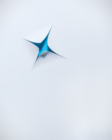 A blue star revealed through a cut or torn bright white paper background.  Lots of negative space for copy or images.  Great for business applications or posters.