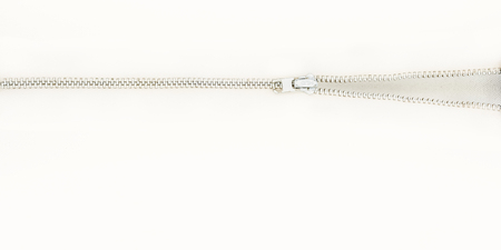 A zipper opening on a bright white background with lots of negative space.  Very minimal.  Wide screen aspect ratio. Standard-Bild