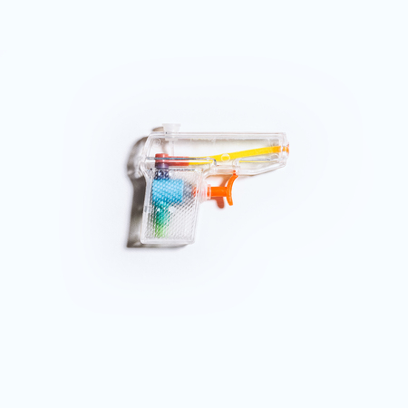 A clear plastic toy squirt gun/water pistol on a bright white background.