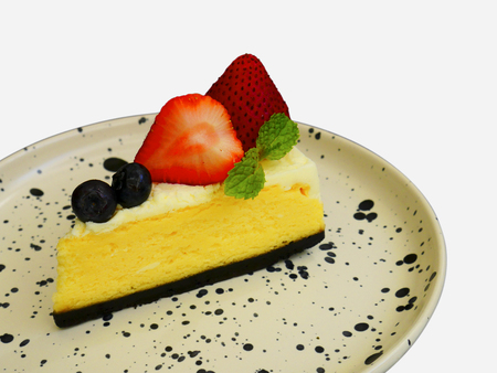 Delicious cheesecake with fresh berries and strawberry on plate isolate on white background. Imagens