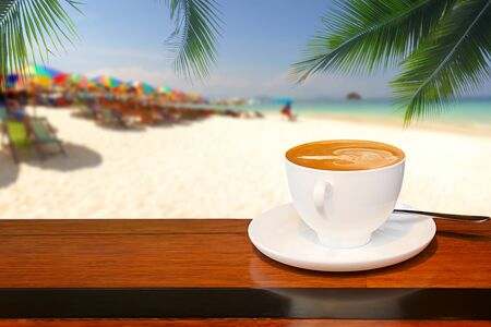 A cup of coffee resting on a wooden table with a coconut leaf background and blurred beach