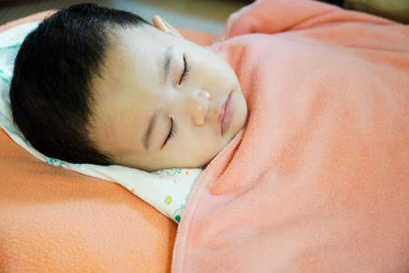 Close-up of a baby sleeping in bed.