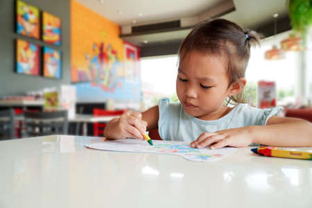 Little child intend coloring with crayons in the classroom.