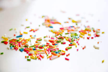 Selective focus colorful sugar sprinkle dots for decoration topping cake and ice cream on the table.