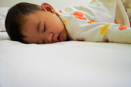 The little boy was sleeping on the bed, sleeping in the prone position.