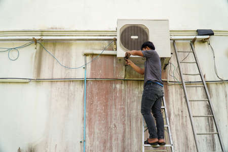 Air conditioner technician is installing the air conditioner on the wall of the house. Stock Photo