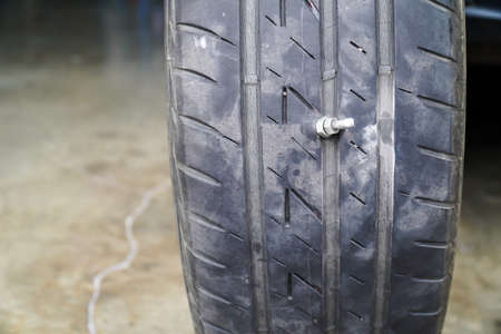 Close-up of the tire where the screw is stuck, causing the tire to leak, The most problems that cause flat tires.