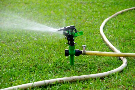 The Watering Automatic sprinkler on Green Lawn