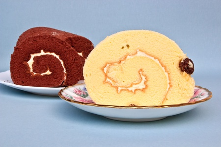 Two Cut Delicious Swiss roll cakes on Plate Stock Photo