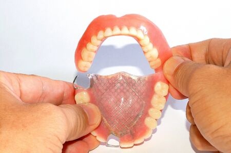 vice: A Vice dentures whole Holding by Hand Stock Photo