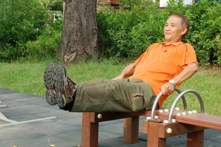 A Man who doing leg lift exercise in Park for Fitness Stock Photo