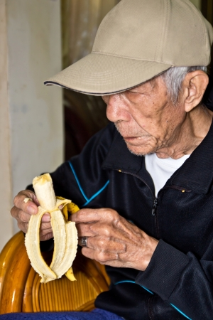 a Chinese Old people who eating banana indoor