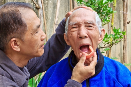 The son who installing Denture for the old Father