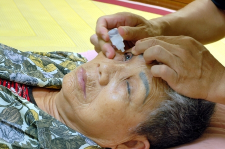 An Elderly woman who Eyedropper Lying in Bed Stock Photo