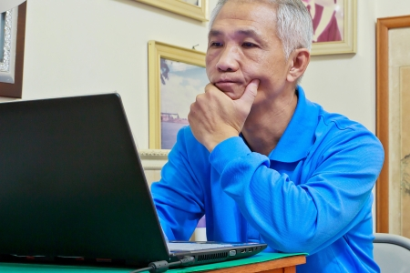 A Middle-aged man who playing computer with confused facial expression Stock Photo