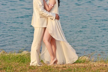 Embrace of newly married Bride and groom lakeside Stock Photo