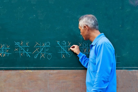 A middle-aged man who Playing wits game on chalkboard photo