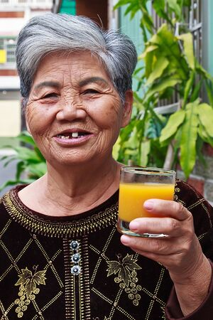 A Chinese Old woman who drinking Orange juice