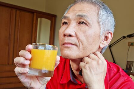 A Chinese middle-aged Man who drinking Orange juice