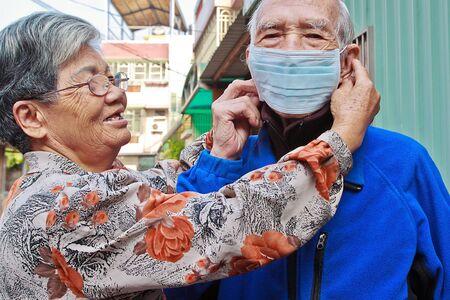 disease prevention: Ayudar a las personas mayores a llevar una m�scara para la prevenci�n de la enfermedad Foto de archivo