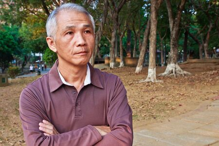 A Contemplative middle-aged Man who Baoxiong in park Stock Photo