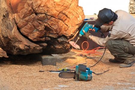carver: Con un tallador de madera que se corta con motosierra