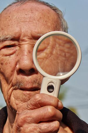 Old man with a magnifying glass