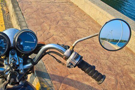 retrovisor: Una motocicleta con el paisaje del embalse de perspectiva en el espejo retrovisor Foto de archivo