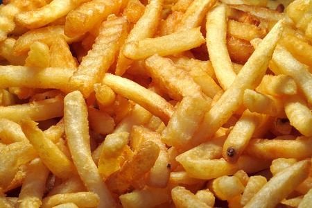 A Pile of Golden yellow French fries for sale