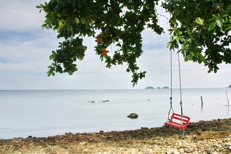 relent: swing rosso sotto l'albero sulla spiaggia Archivio Fotografico