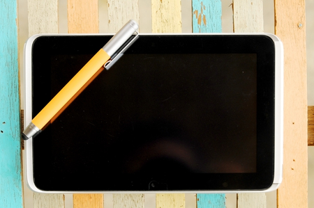 tablet with pen on colorful wooden table  Stock Photo