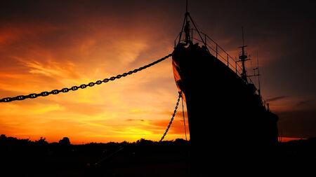 silhouette battleship with golden evening sky Stock Photo