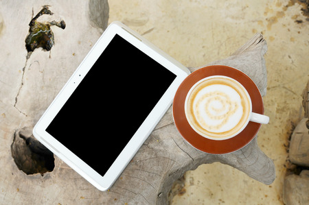 coffee and tablet on folk table  photo