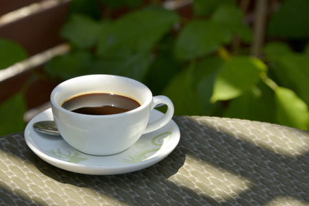 white cup of coffee on aluminium table in garden background