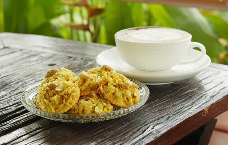 cracker topped corn flake and hot cappuccino coffee on wooden table in terrace  photo