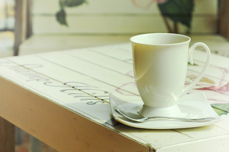 hot coffee on paint wooden table with vintage style  photo