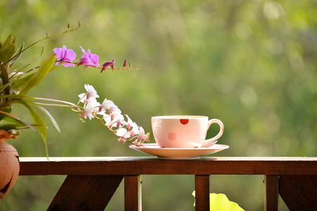 Coffee on rail with orchid flower on terrace with green nature background
